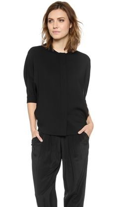 An effortless, yet edgy Alexander Wang blouse with a slouchy silhouette. Fitted cuffs lend a hint of definition to the draped, dolman sleeves, which land at the elbow. Hidden-button placket. Shirttail hem.