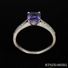 Stylish tanzanite and diamond ring in 18ct white gold. The square cut centre stone is 4 claw set in a simple mount with round cut diamonds channel set into the shoulders. The open mount allows maximum light through the stone enhancing its beautiful colour. £995
