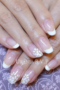 White flower nail art on a white french manicure with golden accents ♡