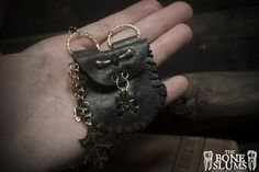 The first thing Midas touched was an oak twig to test his new power, and was delighted and rejoiced that he had been bestowed with such a gift. This medicine pouch is made from a dark, warm grey scrap leather. Adorning it is a phalanges, hand painted gold above it's handmade gold wire clasp. To t...