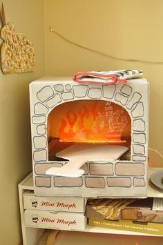 Cardboard pizza oven 2.0! I used string lights in the box below, and laminated tissue paper flames. So much fun for our pizza theme!