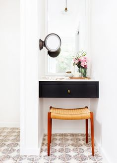 Vanity area in bathroom with fresh flowers and woven stool.