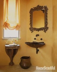 Turning a quirk into an asset, designer Stephen Shubel glorified an oblique wall with the decorative silhouettes of a scallop-shell sink and a Baroque carved mirror frame.   - HouseBeautiful.com