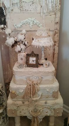 old suitcases painted white and covered with lace dollies, ribbons and beads then stacked to make an end table. Shabby chic, vintage. Great for a wedding too for the guest book and wedding couple photo to be on it.