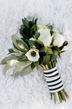 This simple white wedding bouquet, sprinkled with black details, works with any color dress. Anemones like this can make a strong statement.