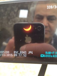 Full screen picture of my camera displaying the eclipsed sun and me reflected.