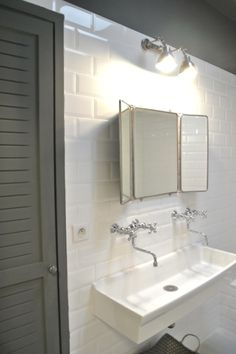 white subway tiles + white trough sink. Wall mount faucets. Vintage 3 panel mirror