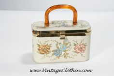 1950s/1960s Lily Bet of Palm Beaches Flower Motif Box Purse with Lucite handle.  This purse is covered in an ivory vinyl with applied colorful floral shapes cut from fabric that is heightened with a gold paint pen that traces the flower outlines, stems and leaf buds.    http://shop.vintageclothin.com/1950s-1960s-Lily-Bet-of-Palm-Beaches-Flower-Motif-Box-Purse-VC1107.htm  #vintage #vintageclothin #vintageclothin.com #forsale #buyme