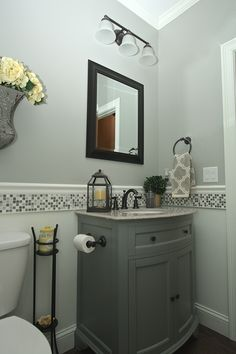 My Guest Bathroom, used mosaic tile under a chair rail to create this unique look. I did this because I wanted a gray furniture style vanity but also wanted the walls to be gray so I needed something to break up the two. Just painted the bottom portion of the wall the same as the trim color and voila! I used yellow as an accent color as the two seem to really work nicely together and were easy to find over the summer as it was a very trendy look.