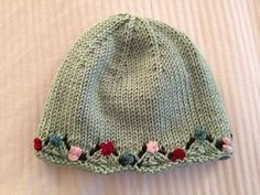 This sweet little hat is embellished with a small amount of Cascade Malizia yarn, which gives the appearance of flowers along the brim. Pretty ribbon could be substituted.
