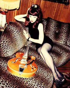 Thee fabulous Poison Ivy of The Cramps on a gorgeous leopard print sofa!