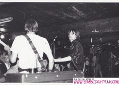 That man again. Mark E Smith of The Fall, onstage at Eric's Club Liverpool in 1978.  A blonde Julian Cope can be seen bottom left, below bass player Marc Riley's arm. (© Michael Finkler)
