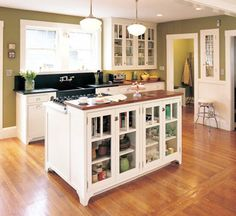 Small kitchen with an island which is a cooker and storage space with a nice glass front cupboard.  #kitchen #island #kitchenisland #breakfastbar #home #inspiration #cupboards #smallkitchen  Image source: www.calfinder.com