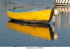 Small yellow boat on blue sea background moored on The Solent at Emsworth. Hampshire. England. In summer evening light - Stock Image