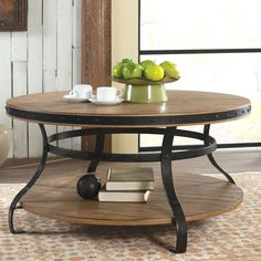Rustic round coffee table with plank table top industrial metal style base and lower shelf.