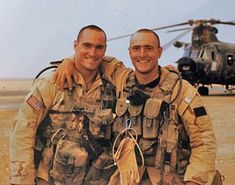 Pat Tillman (left) and his brother Kevin stand in front of a Chinook helicopter in Saudi Arabia before their tour of duty as Army Rangers in Iraq in 2003.