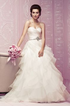 STYLE  4256 DESCRIPTION  Silk Duchesse and Organza bridal gown. Strapless cross over pleated bodice with beaded appliqué at waist. Full Organza ruffled skirt with covered buttons over zipper.  Sweep Train.