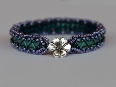 """A beautiful bracelet made with triangle beads by Artbeader """"ButterflySal"""". We love the flower in the middle!"""