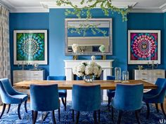 In the dining room of Nadja Swarovski's English countryside home, the bejeweled branch chandelier and the hurricanes on the table are both by Tord Boontje in collaboration with Swarovski. The bespoke table by Whetstone Oak is surrounded by chairs dressed in a Dedar velvet.