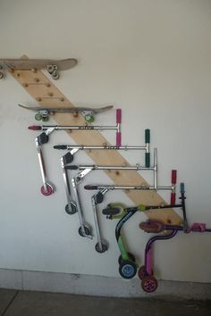 Scooter, skateboard holder. Using vertical space or wall mounts help keep clutter out of the way. This is a genius use of space to store scooters.