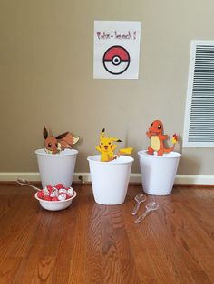 Poke-launch, Pokemon party game. Bought small trashcans, painted wiffle balls (golf/ping pong ball size), 3 serving spoons, and printed out 3 characters on photo paper. Cut out the characters, taped to skewers, and taped to trash can.