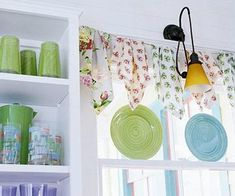 Drape floral hankies on rustic twine to achieve a unique and inexpensive window treatment in your kitchen! Prop plates on the window ledge for an extra pop of color!