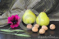 Pears, nuts, spice and pink petunia on the black background