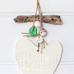 Price:	Starting at $39.95Clay heart handmade in Australia. White earthenware clay glazed with a beautiful gloss glaze.Natural twine with clay pebble beads, driftwood and glass make this a beautiful wall hanging.A band of words of love
