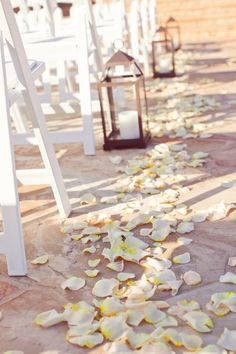 ery few things say romance the way flower petals strewn down the aisle do, except for maybe the soft glow from simple lanterns. Whether you light them or not, the clean glass and simple pillars will add a touch of elegance. #romantic #wedding #aisle #decor