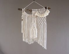 This asymmetrical macramé wall hanging is an exploration in how balance can be found in different ways. Shes a mix of different textures and techniques and is definitely a modern piece of macrame. It is made with 2mm natural undyed cotton rope, knotted with love, and mounted on found wood