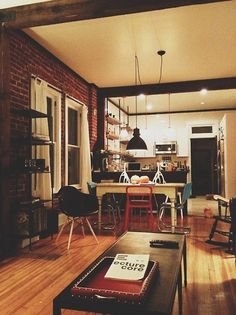 Colton's apartment would look something similar to this, only with a more worn-out look. Definitely see a tired sofa to the right of the coffee table. Love the exposed brick and beams.