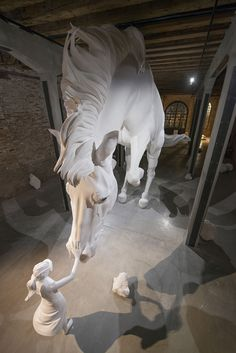 A girl is seen softly touching the nose of a giant, white horse frozen in mid-air within the Argentinian Pavilion of this year's Venice Biennale, a large sculptural work by artist Claudia Fontes. The Horse Problem, and the Argentinian Pavilion, are located within the biennale's Arsenal building, the