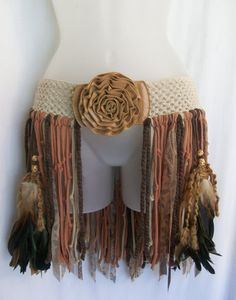 This one of a kind fringe skirt WILL FIT HIPS THAT ARE 36 to about 38 inches. The belt itself is up cycled and has lost a little bit of its stretch but it still is in good working condition ;) The belt on the inside is marked a size XL. Ive added lots of texture and neutral/brown fringe which sways as you walk. There are two handmade beaded feather bundles that hang in the front of the skirt. Perfect for a festival, party or just plain ol everyday wear. She is ready and waiting to be shipped…