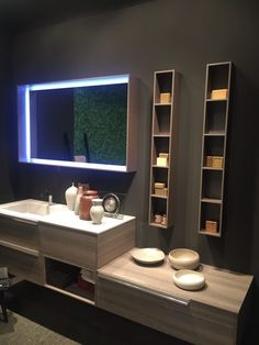 Multiple vanity levels and a combination of open and closed storage makes for a functional and sleek bathroom.