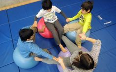 A group of Kohai students work as a team to keep their balance during a gymnastics class.