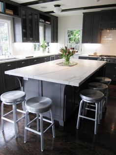 Kitchen with a large grey island topped with Calacatta gold marble surrounded by metal bar stools