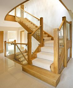 Oak and glass staircase with carpeted runner for noise reduction