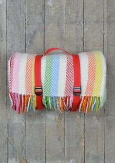 Pure new wool picnic blanket in colourful Rainbow Stripe design, with complimentary red waterproof lining. Easy to transport, this portable rug rolls up easily and is secured with red webbing straps.  Perfect for summer picnics or trips to the beach, this traditional design will last a lifetime.  Hand made in Britain.