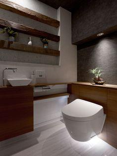 【#ミサワホームイングデザインリフォーム 】トイレのリフォーム。天然の十和田石と表面に様々な削り加工を施した無垢の木材を組み合わせた飾り棚がインテリアのポイントです。梁下部分のダウンライトが壁紙のシックな地模様や観葉植物をドラマチックに浮かび上がらせます。デザイン性はもちろん床掃除のしやすさがフロートタイプの便器&手洗い付き収納キャビネットのメリット。深夜にトイレを利用する場合、眩しすぎる明かりは睡眠の妨げになりやすいので、足元をほんのり照らす人感センサー付のライトを取り入れるなど、健康への配慮も大切です。いつまでも居たくなるレストルームが完成しました。#リフォーム #リノベーション #住まい #インテリア #インテリアデザイン #インテリアコーディネート #マンション #マンションインテリア #マンションリフォーム #マンションリノベーション #トイレ #トイレインテリア #トイレリフォーム #レストルーム #飾り棚 #十和田石 #ナチュラルモダン #トイレ収納 #手洗い器 #アクセントクロス #ミサワホームイング #intelimia Natural Modern Interior, Interior Design Images, Home Renovation, Double Vanity, Toilet, Bathtub, Bathroom, House, Home Decor