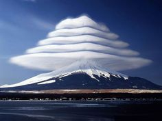 Lenticular clouds over Mount Fuji, Japan. These are stationary lens-shaped clouds that form at high altitudes, usually perpendicular to the...