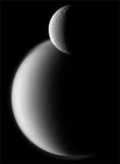 Saturn's moon Rhea in the foreground and Titan