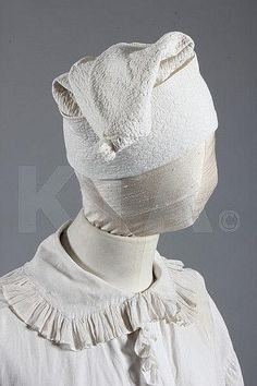 A rare gentleman's nightshirt and nightcap, 18th century, the voluminous shirt of fine white linen with ruffle edging to collar, neck opening and cuffs, Dorset buttons, chest 153cm; the tall conical cap of white cotton with overall false-quilted quatrefoil repeats, fold-over border, tufted tassel to the crown. Click for full-sized image.