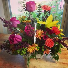 Fall in love with the striking color combo of hot pink, orange & yellow! Designed by Seven Sisters Florist. www.sevensistersflorist.com