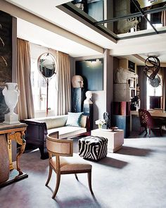 neoclassical sitting area with busts and urns, leopard skin stool, and mirrored ceiling // living rooms