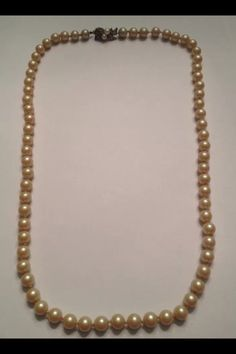 Vintage hand knotted pearl necklace. Silver tone clasp with pearl and rhinestone accents. Necklace is approximately 25 long and pearls about