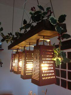 lampara hecha con ralladores de queso y puestas sobre una tabla con plantas