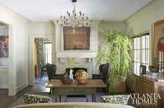 Jared Paul and Kelley Harris's eclectic mix is evident in the formal living room, where a camel hair rug from Istanbul hangs over the mantel while two reupholstered chairs from Davidson's department store provide seating in front of a 19th-century Southern tea table. Chandelier by Gino Sarfatti through Illuminations. Japanese Pendula Tree from Garden Hood.