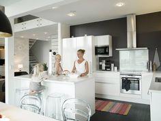 Puustellin keittiössä on valkoiset kiiltävät ovet ja kvartsitasot. Saarekkeessa askartelut ja leipomiset hoituvat näppärästi. Munakoisonsävyinen seinä antaa keittiölle kauniit raamit. Värikäs raidallinen matto on ostettu Hemtexistä. Evianna ja Isella auttavat äitiään leipomisessa.