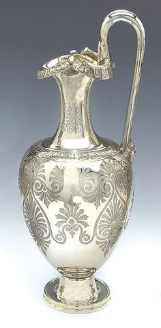 A VICTORIAN SILVER WINE JUG, JOSEPH & ALBERT SAVORY, LONDON 1853 of ewer form with everted triform spout with a lobed rim flanked by two mask heads and a high handle terminating in a female head, the neck and sides engraved with stylised palmettes: