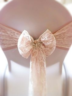 Wedding chairback with lace bow and brooch.